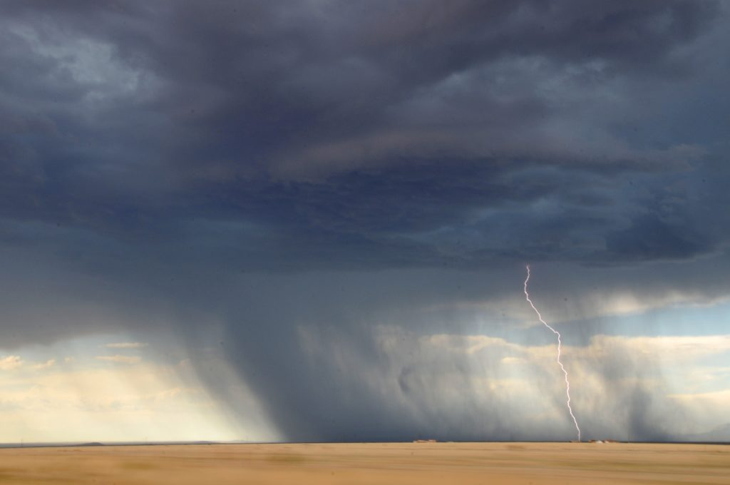 Rain storm over dried crops
